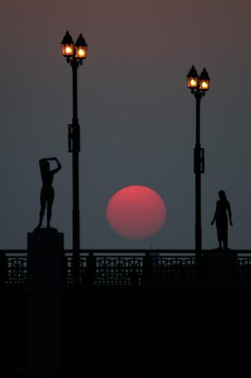 幣舞橋、道東の四季「冬」の像、「春」の像の間に落ちる夕日